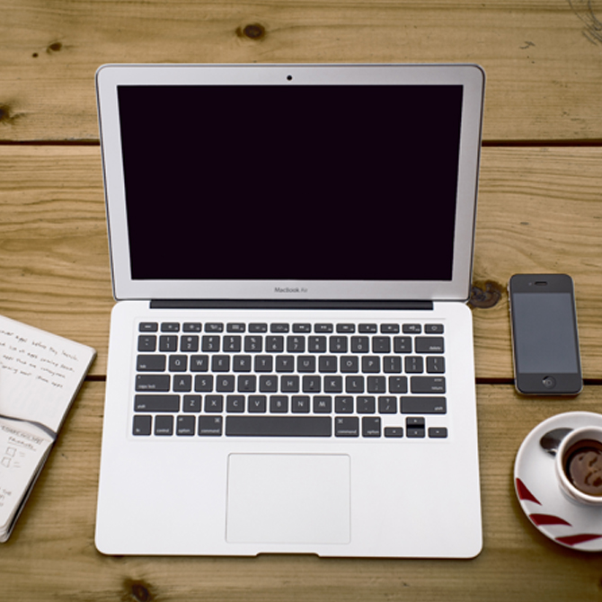 Macbook, notatblokk, telefon og kaffe